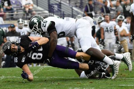 Northwestern wide receiver Bennett Skowronek (88) is tackled by Michigan State linebacker Brandon Bouyer-Randle (26) during the second half of an NCAA college football game, in Evanston, Ill