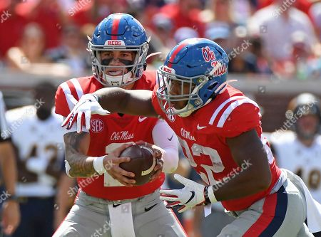 Mississippi quarterback Matt Corral (2) hands the ball off to running back Scottie Phillips (22) during the first half of an NCAA college football game against California in Oxford, Miss