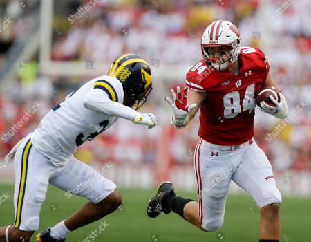 Wisconsin tight end Jake Ferguson (84) runs against Michigan defensive back Vincent Gray during the second half of an NCAA college football game, in Madison, Wis. Wisconsin won 35-14