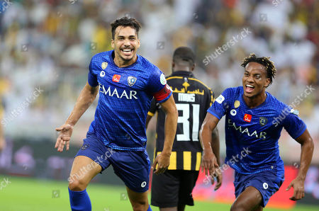 Al-Hilal's Carlos Eduardo (L) celebrates with teammate Andre Carrillo (R) after scoring a goal during the Saudi Arabia Professional League soccer match between Al-Ittihad FC and Al-Hilal S.FC at King Abdullah International Stadium AlJawhra in Jeddah, Saudi Arabia, 21 September  2019.