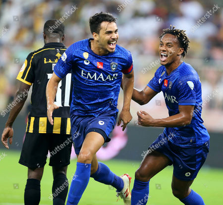 Al-Hilal's Carlos Eduardo (C) celebrates with teammate Andre Carrillo (R) after scoring a goal during the Saudi Arabia Professional League soccer match between Al-Ittihad FC and Al-Hilal S.FC at King Abdullah International Stadium AlJawhra in Jeddah, Saudi Arabia, 21 September  2019.