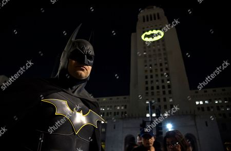 "Tony Bradshaw, of Los Angeles, dressed as Batman, poses in front of a Bat-Signal projected onto City Hall during a tribute to ""Batman"" star Adam West in Los Angeles. The night sky all over the world is lighting up, with an illumination of the famed bat insignia to mark a special anniversary for Batman. DC Comics is carrying off a celebration of ""Batman Day"" to mark the 80th anniversary of the appearance of crimefighter Bruce Wayne and his masked hidden identity. Fan gatherings are planned all over the world"