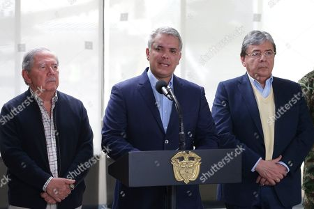 Flanked by Defense Minister Guillermo Boterto, left, and Minister of Foreign Affairs Carlos Holmes Trujillo, Colombia's President Ivan Duque delivers a statement at the CATAM air base in Bogota, Colombia, . Duque has ratcheted up pressure against Venezuela's President Nicolas Maduro in recent weeks accusing him of offering refuge to dissident FARC rebels that decided to break a peace process and take up arms again