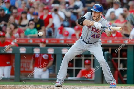 New York Mets' Zack Wheeler hits a sacrifice bunt and then makes it safely to first on a throwing error by Cincinnati Reds first baseman Joey Votto to load the bases in the fifth inning of a baseball game, in Cincinnati