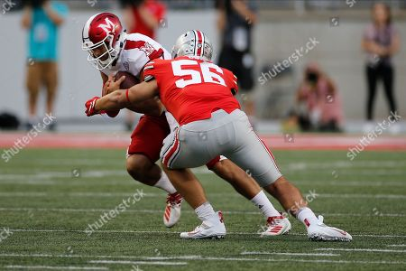 Stock Image of Ohio State defensive lineman Aaron Cox, right, tackles Miami (Ohio) quarterback AJ Mayer during the second half of an NCAA college football game, in Columbus, Ohio