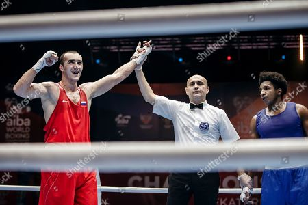 Referee Alessandro Renzini, center, holds up Russia's Muslim Gadzhimagomedov's hand, left, as he is declared the winner over Ecuador's Julio Cesar Castillo Torres during the men's heavy weight final of the AIBA World Boxing Championships in Yekaterinburg, Russia