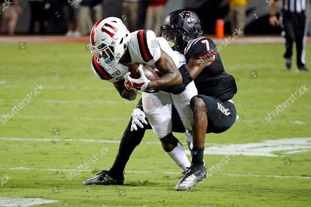 North Carolina State's Chris Ingram (7) ties up Ball State's Justin Hall (11) for a short gain during the first half of an NCAA college football game in Raleigh, N.C