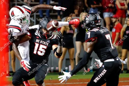 Stock Photo of North Carolina State's C.J. Hart (15) breaks up a pass intended for Ball State's Hassan Littles (16) and it is intercepted by Chris Ingram (7) during the second half of an NCAA college football game in Raleigh, N.C