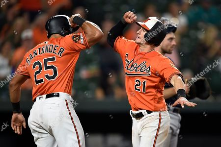 Baltimore Orioles' Austin Hayes, left, is congratulated by Anthony Santander after hitting a two-run home run against the Seattle Mariners during the eighth inning of a baseball game, in Baltimore. The Mariners won 7-6 in 13 innings