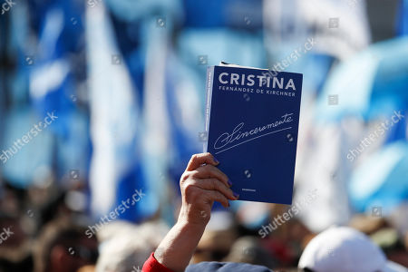 """A supporter holds up a copy of the book """"Sinceramente"""" by former President Cristina Fernandez during the book's presentation in Buenos Aires, Argentina, . Fernandez returns to the public eye in Argentina on Saturday in an event to present her book """"Sincerely"""" just weeks out from presidential election in which the former two-term leader is running as vice presidential candidate in an opposition ticket"""