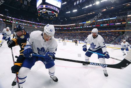 Stock Image of Buffalo Sabres forward Arttu Ruotsalainen (25) and Toronto Maple Leafs forward Trevor Moore (42) compete for the puck in the corner during the second period of an NHL preseason hockey game, in Buffalo, N.Y