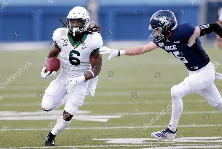 Baylor running back JaMycal Hasty (6) breaks past the tackle attempt by Rice cornerback Andrew Bird (15) during the first half of an NCAA college football game, in Houston