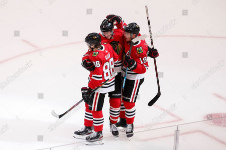 Chicago Blackhawks right wing Patrick Kane, left, celebrates with defenseman Connor Murphy, center, and center Jonathan Toews, right, after scoring a winning goal against the Boston Bruins during overtime of a preseason NHL hockey game, in Chicago