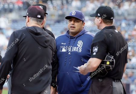 San Diego Padres interim manager Rod Barajas, center, talks during the umpires meeting at home plate before a baseball game against the Arizona Diamondbacks in San Diego