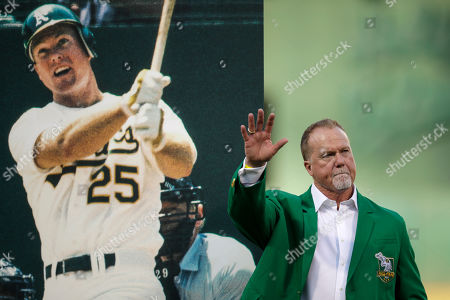 Stock Picture of Former Oakland Athletics player Mark McGwire waves to fans after being inducted into the A's Hall of Fame prior to the team's baseball game against the Texas Rangers, in Oakland, Calif