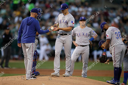 Brock Burke, Chris Woodward. Texas Rangers pitcher Brock Burke, center, hands the ball to manager Chris Woodward, left, while being removed during the first inning of the team's baseball game against the Oakland Athletics, in Oakland, Calif