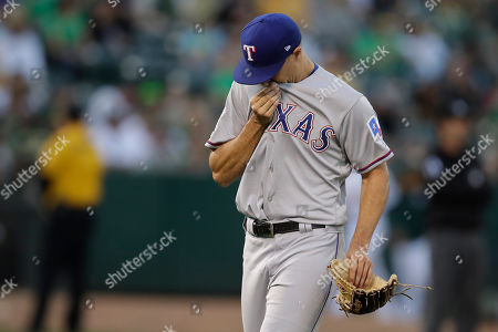 Texas Rangers pitcher Brock Burke wipes his face after being removed during the first inning of the team's baseball game against the Oakland Athletics, in Oakland, Calif