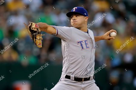 Texas Rangers pitcher Brock Burke works against the Oakland Athletics during the first inning of a baseball game, in Oakland, Calif
