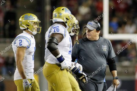 Stock Photo of UCLA head coach Chip Kelly, right, speaks with wide receiver Kyle Philips, left, offensive lineman Christaphany Murray, second from the left, and wide receiver Jaylen Erwin during the second half of an NCAA college football game against Washington State in Pullman, Wash