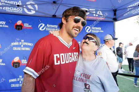 Stock Image of Quarterback of the NFL football Jacksonville Jaguars and former Washington State quarterback Gardner Minshew, left, takes a photograph with fan Mary Deccio, who is wearing a Minshew themed mustache, before an NCAA college football game between Washington State and UCLA in Pullman, Wash