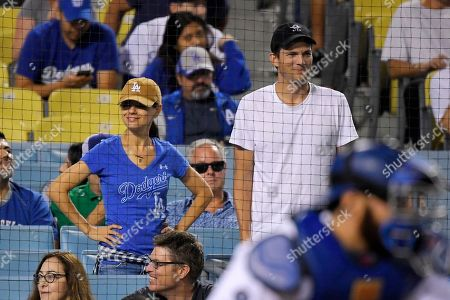 Stock Image of Mila Kunis, Ashton Kutcher. Actors Mila Kunis, left, and Ashton Kutcher watch during a baseball game between the Los Angeles Dodgers and the Colorado Rockies, in Los Angeles