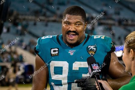 Wearing a fake stick-on mustache, Jacksonville Jaguars defensive end Calais Campbell, left, is interviewed by Erin Andrews, Sideline Reporter for Fox NFL, after an NFL football game between the Jacksonville Jaguars and the Tennessee Titans, in Jacksonville, Fla