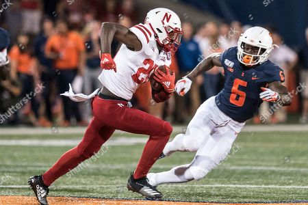 Nebraska's Maurice Washington (28) runs with the ball as Illinois' Tony Adams (6) defends in the first half of an NCAA college football game, in Champaign, Ill