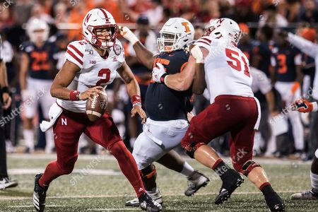 Nebraska's Adrian Martinez (2) is pressured by Illinois' Jamai Milan (55) in the first half of an NCAA college football game, in Champaign, Ill