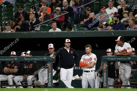 Baltimore Orioles first baseman Chris Davis, center left, talks with right fielder Trey Mancini, center right, in the dugout during the second inning of a baseball game against the Toronto Blue Jays, in Baltimore