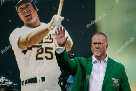 Former Oakland Athletics Mark McGwire waves to fans after being inducted into the A's Hall of Fame prior to the baseball game against the Texas Rangers, in Oakland, Calif