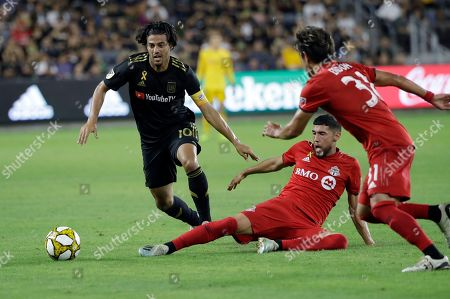 Carlos Vela, Jonathan Osorio. Los Angeles FC's Carlos Vela, left, is defended by Toronto FC's Jonathan Osorio, bottom center, during the second half of an MLS soccer match, in Los Angeles
