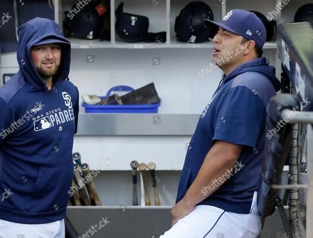 San Diego Padres interim manager Rod Barajas, right, enjoys a moment with relief pitcher Kirby Yates in the dugout before a baseball game against the Arizona Diamondbacks in San Diego