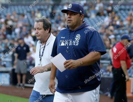 San Diego Padres interim manager Rod Barajas, right, brings out the lineup for the umpires meeting before a baseball game against the Arizona Diamondbacks in San Diego