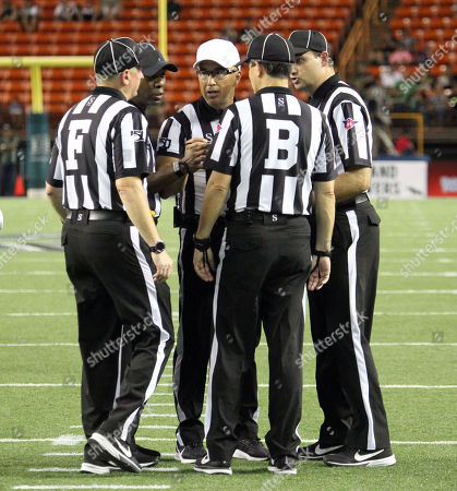Referee Scott Campbell confers with his crew on a call during the game between the Hawaii Rainbow Warriors and the Central Arkansas Bears at Aloha Stadium in Honolulu, HI - Michael Sullivan/CSM