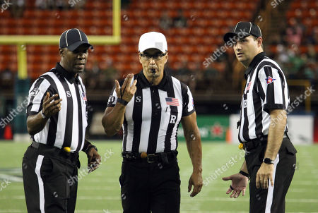 Referee Scott Campbell motions to other officials to come for a meeting during the game between the Hawaii Rainbow Warriors and the Central Arkansas Bears at Aloha Stadium in Honolulu, HI - Michael Sullivan/CSM