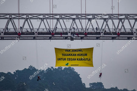 Greenpeace activists hang a giant banner 'Jokowi, please uphold the law to prevent forest fires' on the Kahayan bridge during a protest, in Palangkaraya, Central Kalimantan, Indonesia, 22 September 2019. Dozens of activists staged a protest urging the government to bring plantation companies that responsible to the forest fires to the legal court. Firefighters, military personnel and water-dropping helicopters are deployed to douse the land fires in Sumatra and Borneo that caused thick haze in the neighboring countries, Singapore and Malaysia.