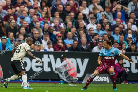 Stock Photo of Mark Noble (Capt) (West Ham) looking on at Ashley Young (Capt) (Man United) with the ball during the Premier League match between West Ham United and Manchester United at the London Stadium, London