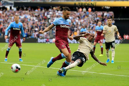 West Ham's Winston Reid, left, and Manchester United's Ashley Young vie for the ball during the English Premier League soccer match between West Ham and Manchester United at London stadium in London