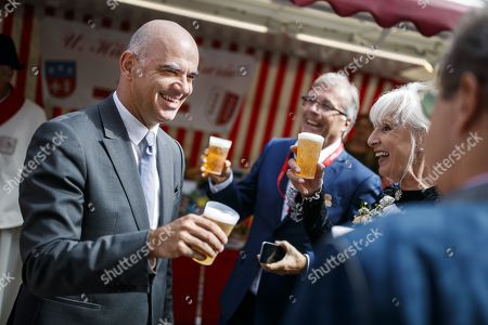 Swiss Federal Councilor Alain Berset (L) shares a beer as he attends with some 1,500 participants during the closing parade of the Federal Festival of Traditional Music (Fete Federale de la Musique Populaire) in Crans-Montana, Switzerland, 22 September 2019. The FFMP runs from 19 to 22 September.