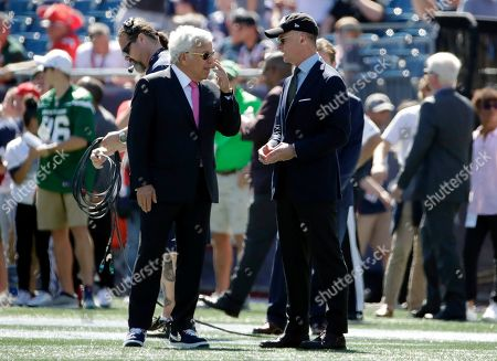 New England Patriots owner Robert Kraft, left, and New York Jets owner Woody Johnson speak on the field before an NFL football game, in Foxborough, Mass
