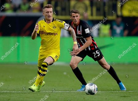 Dortmund's Marco Reus, left, and Frankfurt's Erik Durm, right, challenge for the ball during the Bundesliga soccer match between Eintracht Frankfurt and Borussia Dortmund in the Commerzbank Arena in Frankfurt, Germany, Sunday, Sept.22, 2019