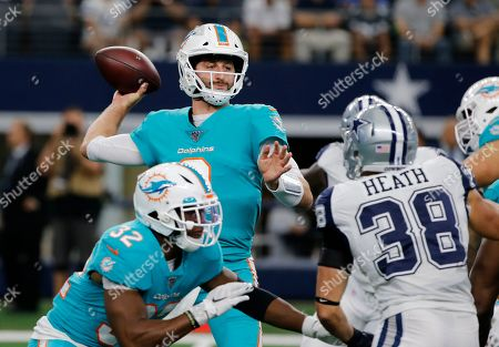 Miami Dolphins quarterback Josh Rosen (3) throws a pass as running back Kenyan Drake (32) provides protection as Dallas Cowboys' Jeff Heath (38) rushes in the first half of a NFL football game in Arlington, Texas
