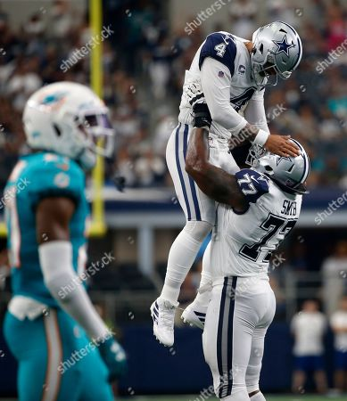 Dallas Cowboys quarterback Dak Prescott (4) is lifted by offensive tackle Tyron Smith (77) after throwing a touchdown pass to wide receiver Amari Cooper (not shown) in the second half of a NFL football game against the Miami Dolphins in Arlington, Texas
