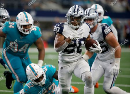 Dallas Cowboys running back Tony Pollard (20) runs the ball as Miami Dolphins middle linebacker Raekwon McMillan (52) and Christian Wilkins (94) give chase in the second half of an NFL football game in Arlington, Texas