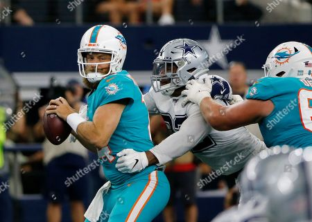 Miami Dolphins quarterback Ryan Fitzpatrick, left, attempts to throw a pass under pressure from Dallas Cowboys' Dorance Armstrong (92) in the first half of an NFL football game in Arlington, Texas