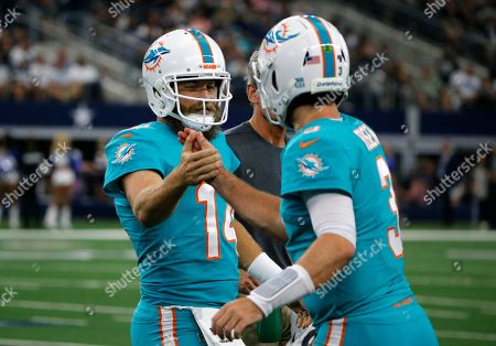 Miami Dolphins' Ryan Fitzpatrick high-fives with Josh Rosen, right, as he walks off the field in the first half of an NFL football game against the Dallas Cowboys in Arlington, Texas