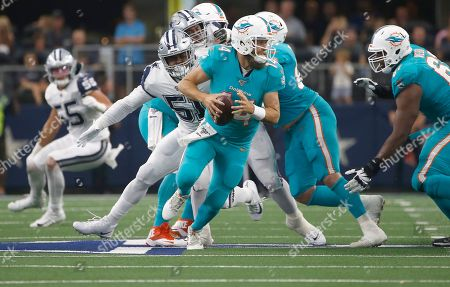 Miami Dolphins quarterback Ryan Fitzpatrick (14) scrambles against the Dallas Cowboys during the first half of a NFL football game in Arlington, Texas