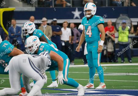 Miami Dolphins quarterback Ryan Fitzpatrick (14) looks on against the Dallas Cowboys in the first half of a NFL football game in Arlington, Texas