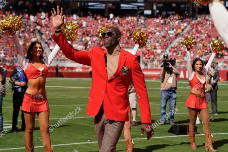 Former San Francisco 49ers wide receiver Terrell Owens waves during a ceremony as he is inducted into the team's Hall of Fame during halftime of an NFL football game between the 49ers and the Pittsburgh Steelers in Santa Clara, Calif