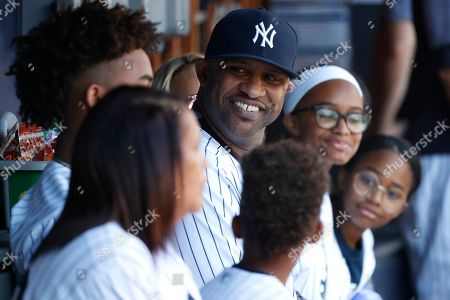 New York Yankees' CC Sabathia, with his family, sits in the dugout before being honored before a baseball game against the Toronto Blue Jays, in New York